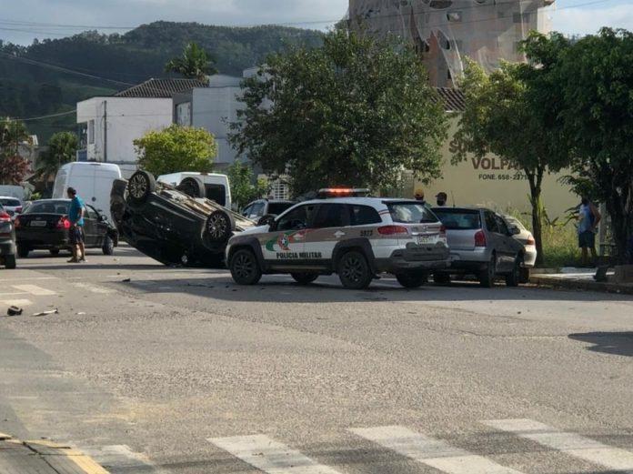 #Pracegover Na foto, carro da polícia e um veículo capotado