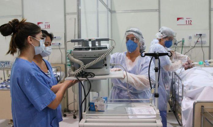 #Pracegover Na foto, profissionais da saúde manuseando equipamentos de UTI