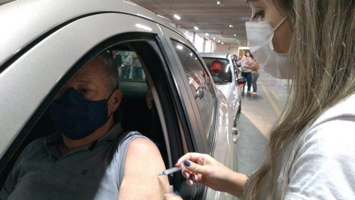 #Pracegover Na foto, profissional da saúde aplicando vacina em um idoso