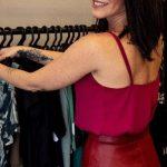 #Pracegover Na foto, Juliana Luque aparece mexendo em roupas