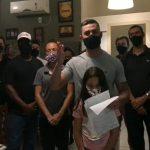 #Pracegover Na foto, empresário aparece com os funcionários e uma criança, todos usando máscara