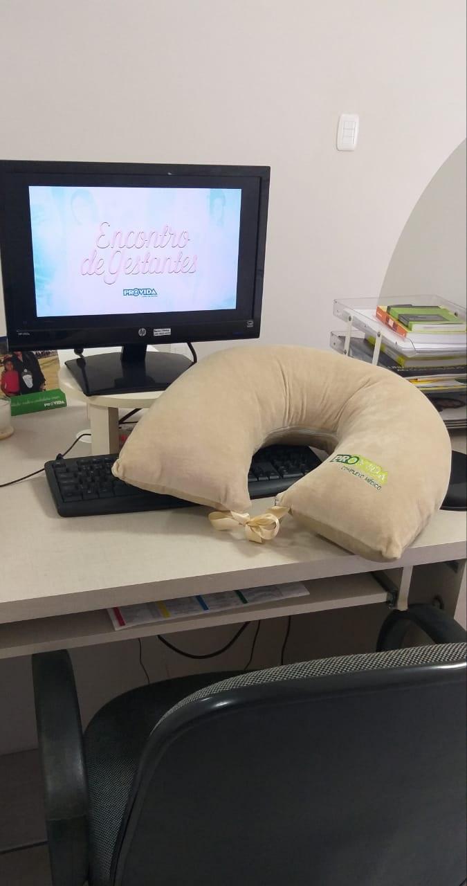 #Pracegover Na foto, tela de um computador, teclado e uma almofada de pescoço sobre a mesa