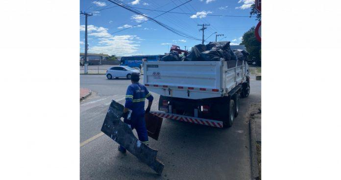 #pracegover Na foto, um homem segura entulhos para botar em um caminhão
