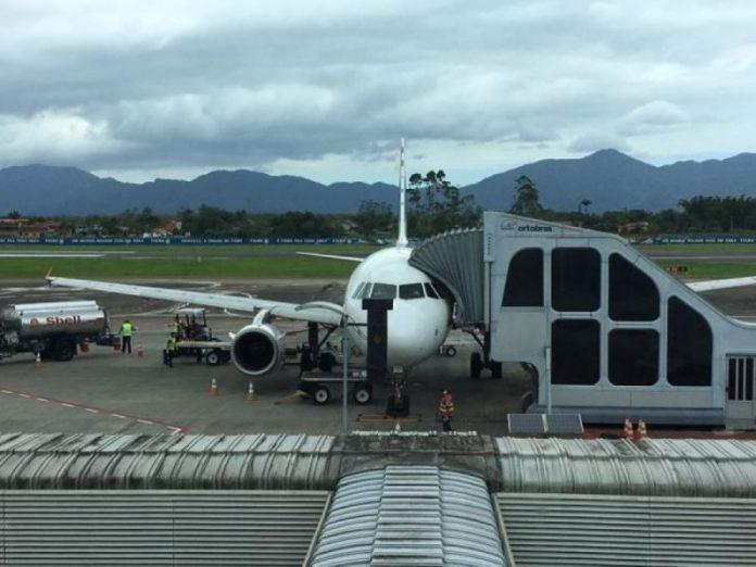 #pracegover Na foto, avião ao lado da plataforma de embarque e desembarque de passageiros