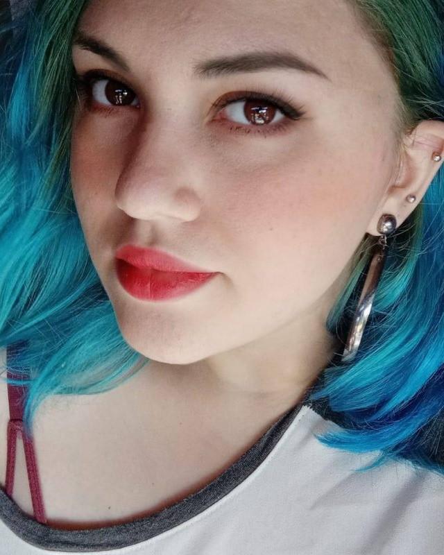 #Pracegover Na foto, Géssica aparece com um leve sorriso e cabelo pintado de azul