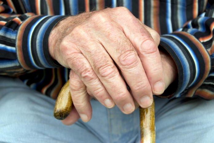 #Pracegover Na foto, uma idosa sentada se apoiando em uma bengala