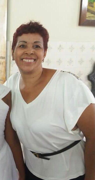#Pracegover Foto: na imagem há uma mulher sorridente e de roupa branca