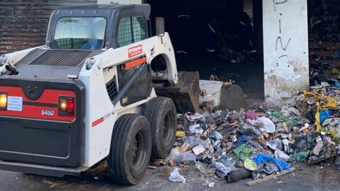 #Pracegover Na foto, máquina retirando lixo e entulho dentro de um edifício