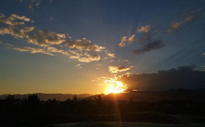 #Pracegover Na foto, céu com poucas nuvens e sol se pondo atrás de um morro