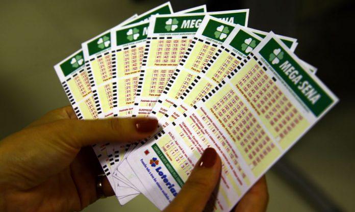 #pracegover Na foto, uma mulher segura vários bilhetes de loteria