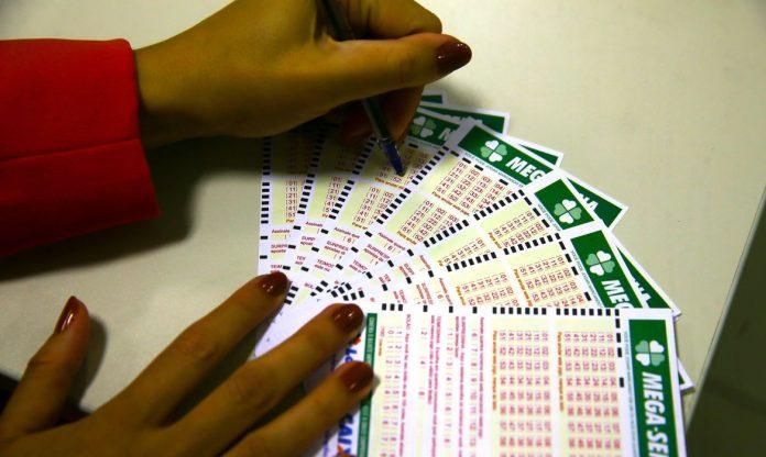 #pracegover Na foto, uma mulher preenchendo vários bilhetes de loteria