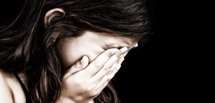 #pracegover Na foto, uma menina está chorando e com as mãos tapando o rosto