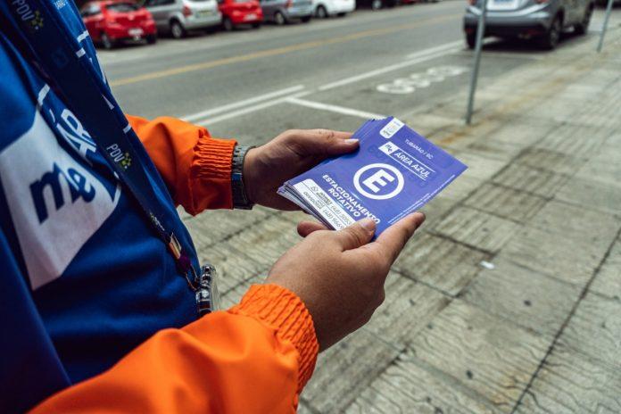 #Pracegover Na foto, um monitor segura um cartão do estacionamento