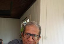 #pracegover Na foto, Luiz Henrique aparece sentado, usa camisa cinza óculos de grau com armação escura e está sorrindo