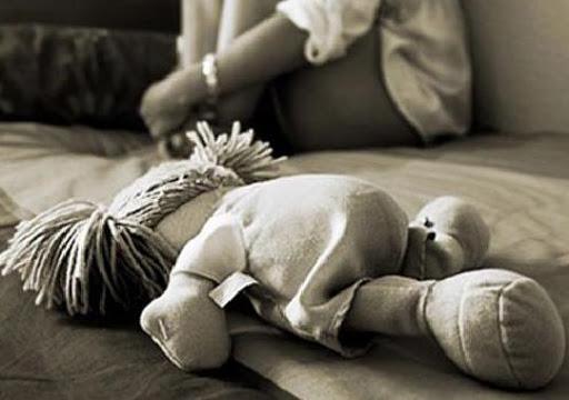 #Pracegover Na foto, uma boneca e ao fundo uma menina
