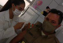 #pracegover Na foto, Sargento Édimo Antônio Garcia aparece recebendo a vacina