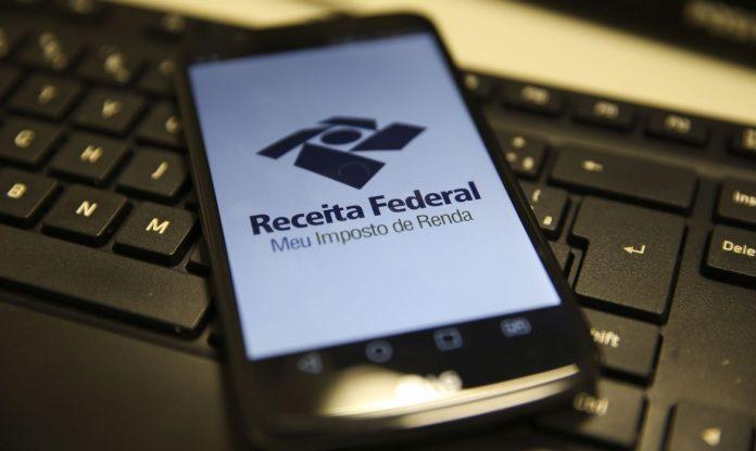 #PraCegoVer Na foto, uma celular com a tela aberta em um programa da Receita Federal