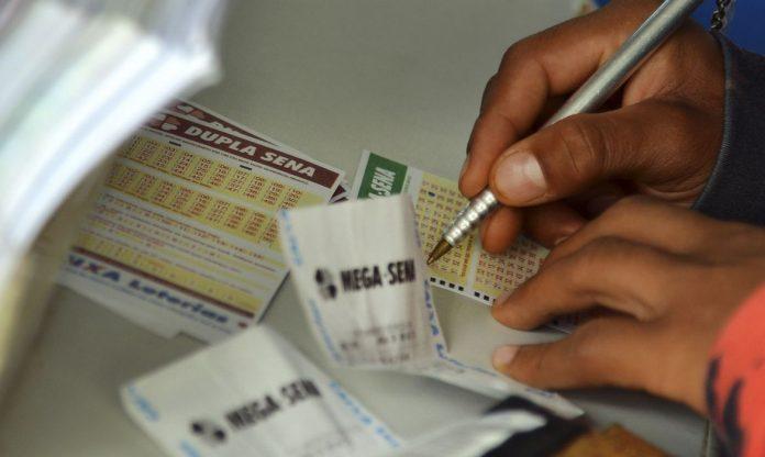 #Pracegover Na foto, uma pessoa marcando um bilhete de loteria
