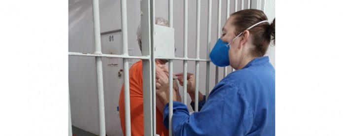 #pracegover Na foto, enfermeira vacina detento em Tubarão