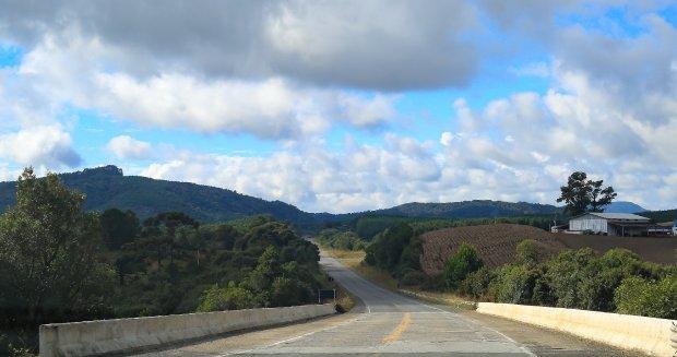 #Pracegover Na foto, uma rodovia asfaltada, em volta um campo verde, céu com algumas nuvens