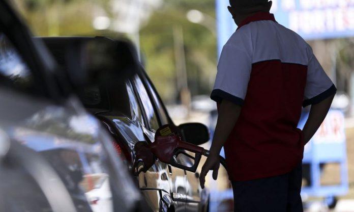 #pracegover Na foto, um frentista abastecendo um veículo em um posto de combustível