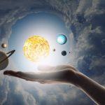 """#Pracegover Na foto, uma montagem de um pessoa """"segurando"""" planetas e o sol"""