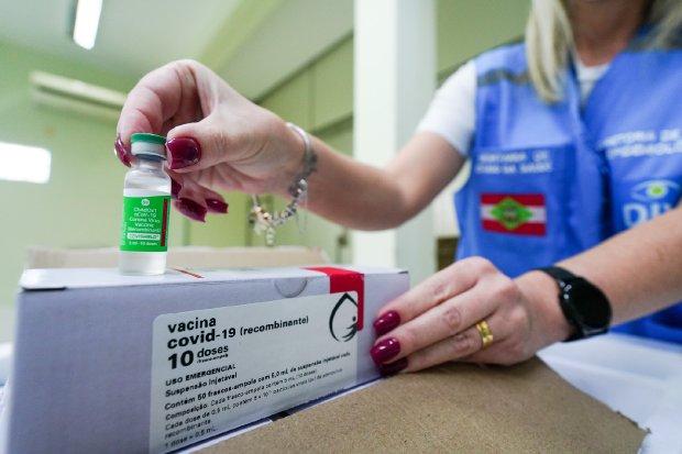#Pracegover Na foto, profissional de saúde segurando um frasco de vacina e uma embalagem de papelão