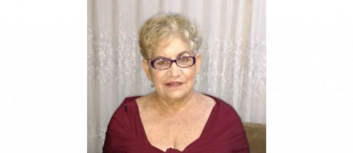 #pracegover Na foto, Dona Linda aparece com um leve sorriso, usa uma blusa e óculos de de cores bordô