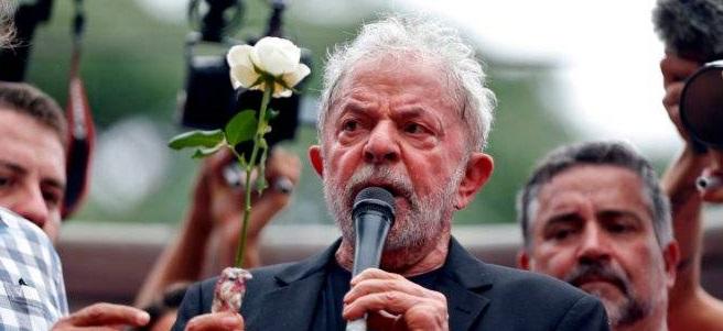 #pracegover Na foto, Lula segura um microfone e uma flor durante discurso