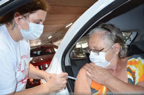 #Pracegover Na foto, uma profissional vacinando idosa em Tubarão