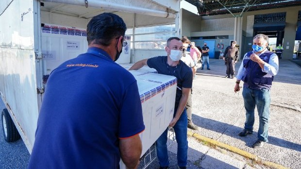 #Pracegover Na foto, homens carregando caixas com as doses da vacina