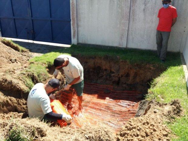 #Pracegover Na foto há dois homens em um buraco quadrado analisando o solo