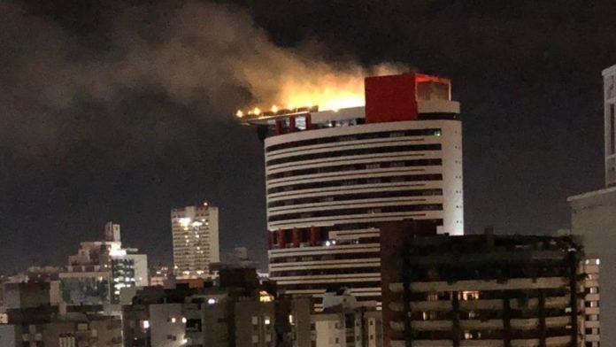 #Pracegover Na foto, fumaça de incêndio sendo expelida pela cobertura do edifício