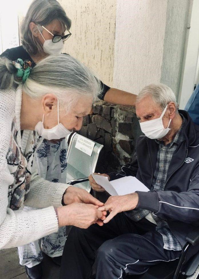 #Pracegover Na foto, idosa aparece colocando uma aliança em um idoso