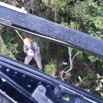 #pracegover Na foto, vista de cima do helicóptero. Um resgatista descendo de rapel e na mata um jovem aguardando o resgate