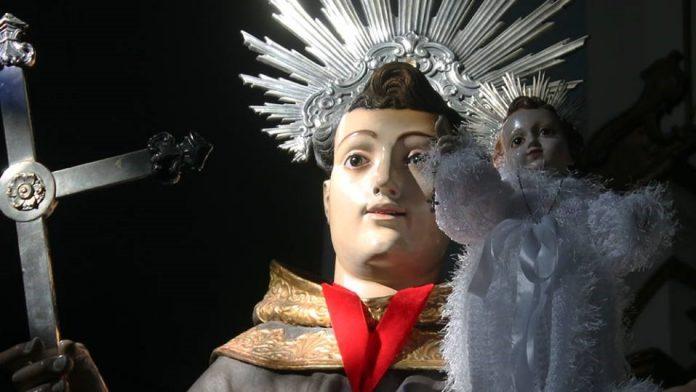 #Pracegover Na foto, imagem de Santo Antônio usando usando uma coroa e segurando uma cruz