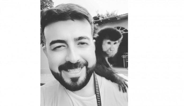 #Pracegover Na foto, Murilo aparece sorrindo e está de barba e com um macaquinho no ombro