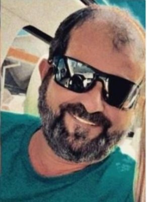 #Pracegover Foto: na imagem há um homem de camiseta e óculos escuros