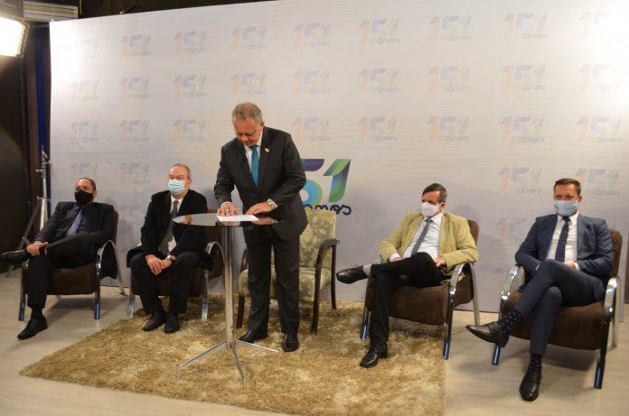 #Pracegover Foto: na imagem há um homem em pé, quatro homens sentados, uma mesa, caneta e folhas