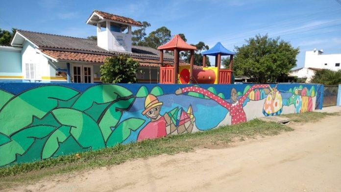 #Pracegover Na foto, muro pintado cores predominantes em verde, azul e rosa