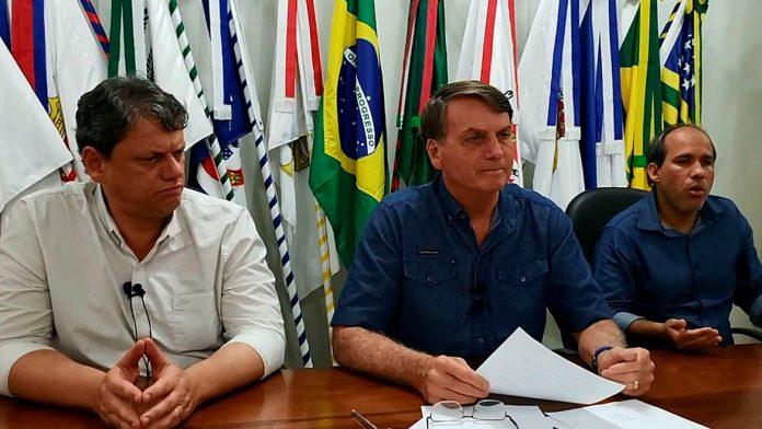 #Pracegover Na foto, Bolsonaro está sentado em frente a uma mesa e acompanhado de outras duas pessoas