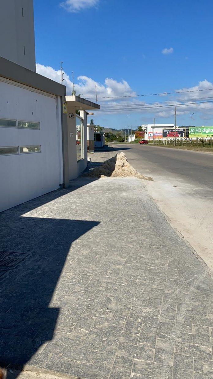 #Pracegover Foto: na imagem há casas, rua e material de construção na calçada
