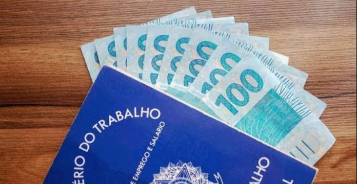 #Pracegover Na foto, carteira de trabalho e dinheiro sobre uma mesa