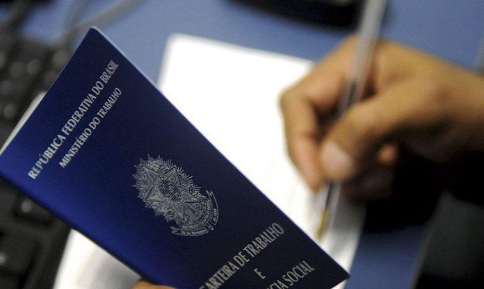 #Pracegover Foto: na imagem há uma carteira de trabalho, uma mão e uma caneta