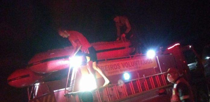 #Pracegover Na foto, Bombeiros em cima de um bote inflável, segurando lanternas