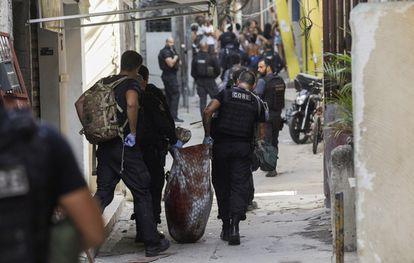 #pracegover Na foto, policiais levam um corpo enrolado em um pano