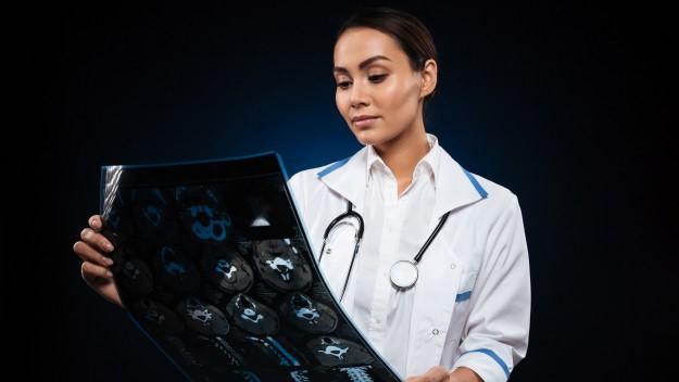 #Pracegover Na foto, médica olhando radiografia de um pulmão