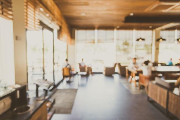 #Pracegover Na foto, escritório com várias mesas e cadeira e pessoas trabalhando