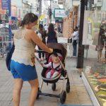 #Pracegover Na foto, mulher empurra umcarrinho de bebê enquanto olha uma vitrine