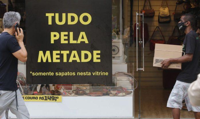 #Pracegover Foto: na imagem há uma placa, uma vitrine e pessoas